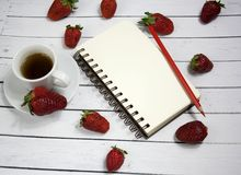 Une page blanche de carnet sur un fond romantique rustique de fond en bois avec des fraises Une cuvette de café de matin Endroit  Photographie stock