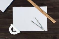 Une page blanche de papier et d'accessoires pour le mensonge de dessin sur la table Photos stock
