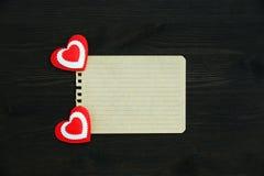Une page de papier blanche et deux coeurs sur un fond en bois Photo libre de droits