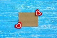 Une page de papier blanche et deux coeurs sur un fond en bois bleu Photographie stock