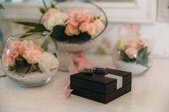 Une paire argente des boutons de manchette dans la boîte sur le fond blanc avec la fleur et le boutonniere, les accessoires du `  Photos stock