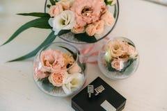 Une paire argente des boutons de manchette dans la boîte sur le fond blanc avec la fleur et le boutonniere, les accessoires du `  Photographie stock