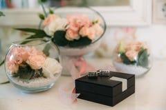 Une paire argente des boutons de manchette dans la boîte sur le fond blanc avec la fleur et le boutonniere, les accessoires du `  Image libre de droits