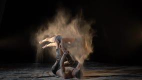 Une paire d'acrobates en farine, un homme jette une femme sur ses jambes, mouvement lent clips vidéos