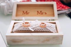 Une paire d'anneaux de mariage d'or se situant dans une boîte en bois blanche Décoration de mariage Symbole de famille, d'unité e Images stock