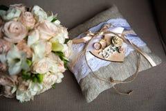 Une paire d'anneaux de mariage sur un oreiller de toile de jute photo libre de droits