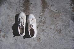 Une paire d'espadrille ou de chaussures blanche de vintage sur le rez-de-chaussée de ciment Photographie stock