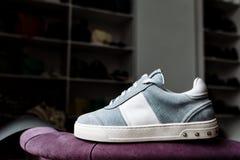 Une paire d'espadrilles bleues de suède sur une semelle blanche avec les accents blancs sur un fond de magasin photos stock
