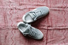 Une paire d'espadrilles bleues de suède sur une semelle blanche avec les accents blancs sur un fond rose photo stock