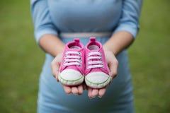 Une paire d'espadrilles roses d'enfant en bas âge dans les mains de la femme enceinte Photographie stock libre de droits