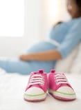 Une paire d'espadrilles roses d'enfant en bas âge près d'une femme enceinte, foyer o Photos libres de droits