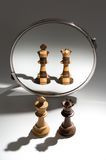 Une paire d'un roi blanc et d'une reine noire regarde dans un miroir pour se voir comme une paire colorée noire et blanche Photos libres de droits