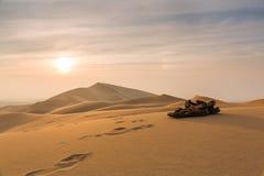 Une paire de bascules électroniques brunes dans le désert au coucher du soleil Image stock