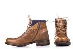 Une paire de bottes usées d'isolement sur un fond blanc Photographie stock libre de droits