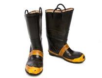 Une paire de bottes usées du feu sur le blanc Photographie stock libre de droits