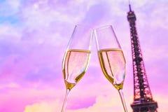 Une paire de cannelures de champagne avec les bulles d'or sur le coucher du soleil brouille le fond d'Eiffel de tour Image libre de droits