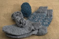 Une paire de chaussette et de bobines traditionnelles de laine sur un backgro de toile de jute Images libres de droits