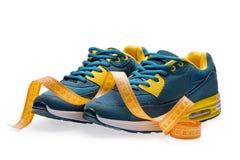 Une paire de chaussures bleues de sports avec la bande de mesure Photos libres de droits
