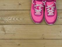 Une paire de chaussures roses du ` s de femmes sur le plancher des planches en bois Images stock