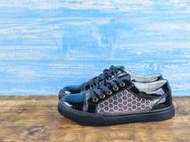 Une paire de chaussures sportives noires de fille de style sur le plancher en bois Photo stock