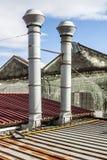 Une paire de cheminées métalliques sur un dessus de toit d'une usine Image libre de droits