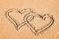 Une paire de coeurs peints sur le sable en été à la mer Image stock