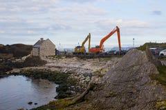 Une paire de grues utilisées pour draguer le petit port chez Ballintoy sur la côte du nord d'Antrim de l'Irlande du Nord une jour Image libre de droits