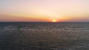 Une paire de kitesurfers nage en mer pendant le coucher du soleil, tir aérien banque de vidéos