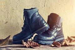 Une paire de la botte des hommes en cuir noirs avec la feuille sèche sur la texture en bois et de papier Images stock