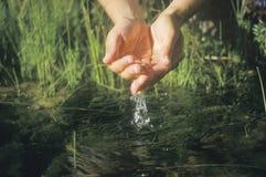 Une paire de mains entrant dans une rivière pour obtenir l'eau propre images stock