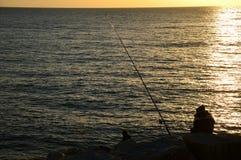 Une paire de pêcheurs à la ligne dans le coucher du soleil Photo libre de droits