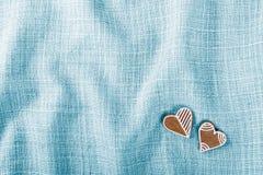 Une paire de pains d'épice fleuris doux pour la bonne chance sur un tissu bleu Photographie stock