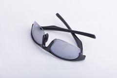 Une paire de verres de soleil noirs et sportifs sur une surface blanche images libres de droits