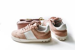 Une paire des chaussures roses de suède avec les accents blancs et d'un sac à l'arrière-plan sur un fond blanc image libre de droits