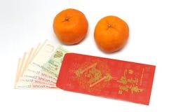 Une paire des mandarines et d'une enveloppe rouge avec des notes d'argent de Singapour à l'intérieur Photographie stock