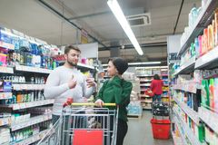 Une paire positive est dans le département de ménage du supermarché et communique Achats de famille à un supermarché photo stock