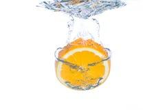 Une part orange tombant dans l'eau photographie stock libre de droits