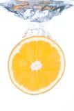 Une part orange tombant dans l'eau image stock