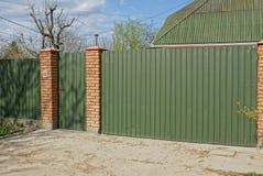 Une partie d'une barrière de long fer de couleur verte et une porte fermée dans la rue près de la route photographie stock
