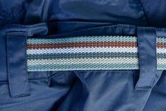 Une partie d'une ceinture rayée faite de tissu sur le pantalon bleu photographie stock libre de droits