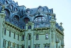 Une partie d'une grande belle maison avec un toit gris et un mur vert avec des balcons et fenêtres contre le ciel image stock