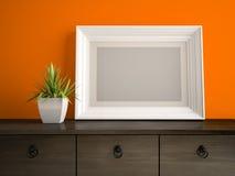 Une partie d'intérieur avec le cadre blanc et le mur orange 3D rendant 2 Photographie stock libre de droits
