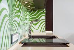 Une partie d'intérieur moderne de cuisine avec le bassin images stock
