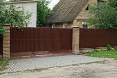 Une partie d'une longue barrière brune métallique et d'une grande porte dehors dans l'herbe photos libres de droits