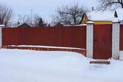Une partie d'une longue barrière rouge en métal et une porte fermée dans l'extérieur blanc de neige photos stock