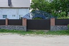 Une partie d'une longues barrière et porte brunes de fer et pierre dans la rue près de la route du sable image stock