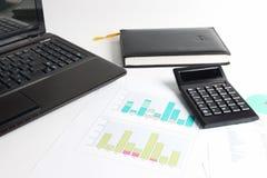 Une partie d'ordinateur portable, calculatrice, diagrammes, graphiques, documents Photos libres de droits