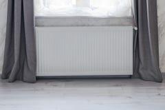 Une partie d'une salle lumineuse avec le radiateur d'escroquerie de chauffage installé sous la fenêtre image libre de droits