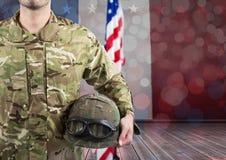 Une partie d'un soldat tenant un casque sur un fond de drapeau américain Photo stock