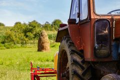 Une partie d'un tracteur et une pile de foin sur un flanc de coteau images stock